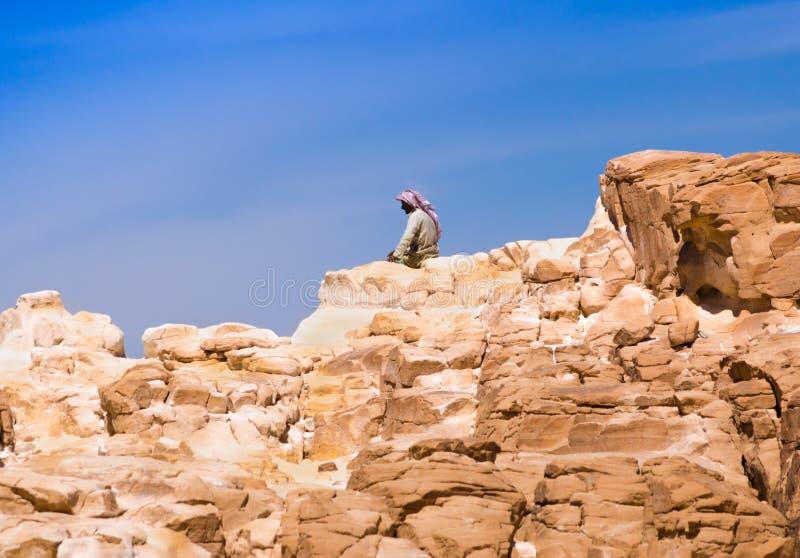 Beduiński obsiadanie na szczycie wysoka kamień skała przeciw niebieskiemu niebu w Egipt Dahab południe Synaj obraz stock