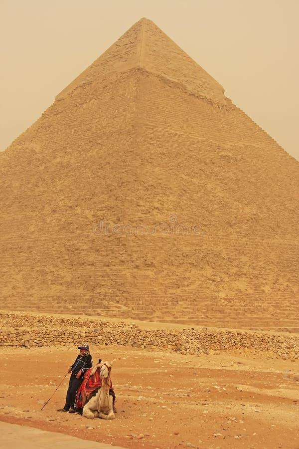Beduiński odpoczynkowy pobliski ostrosłup Khafre podczas burzy piaskowa, Kair fotografia stock