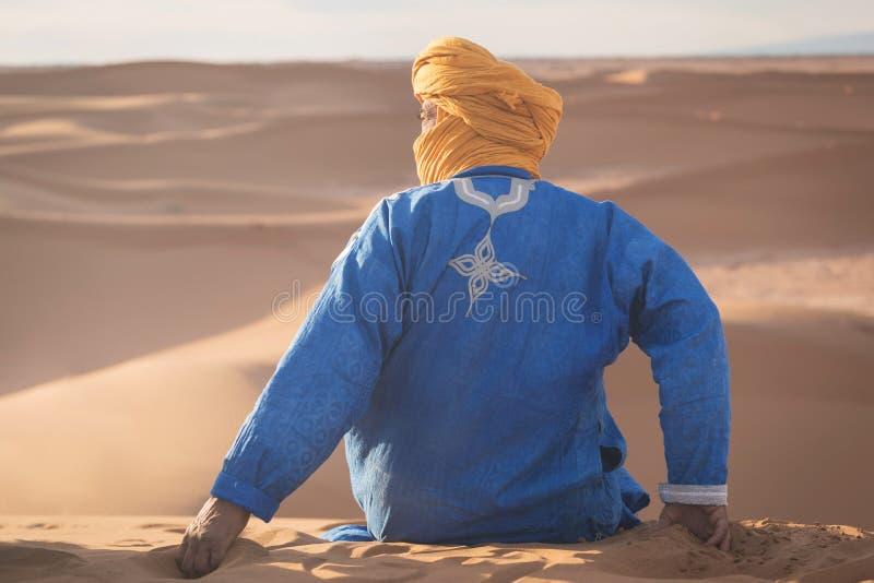 Beduin nomad, Sahara, Maroko Portret koczownika beduińskiego z kolorowym turbanem i wielkim uśmiechem siedzącym na wydmie piaskow zdjęcia royalty free