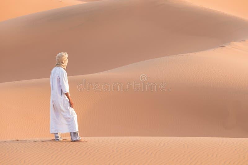 Beduin w drodze przez piaszczystą pustynię Piękny zachód słońca z dużymi wydmami na Saharze, Maroko Koczownik z sylwetki zdjęcia stock