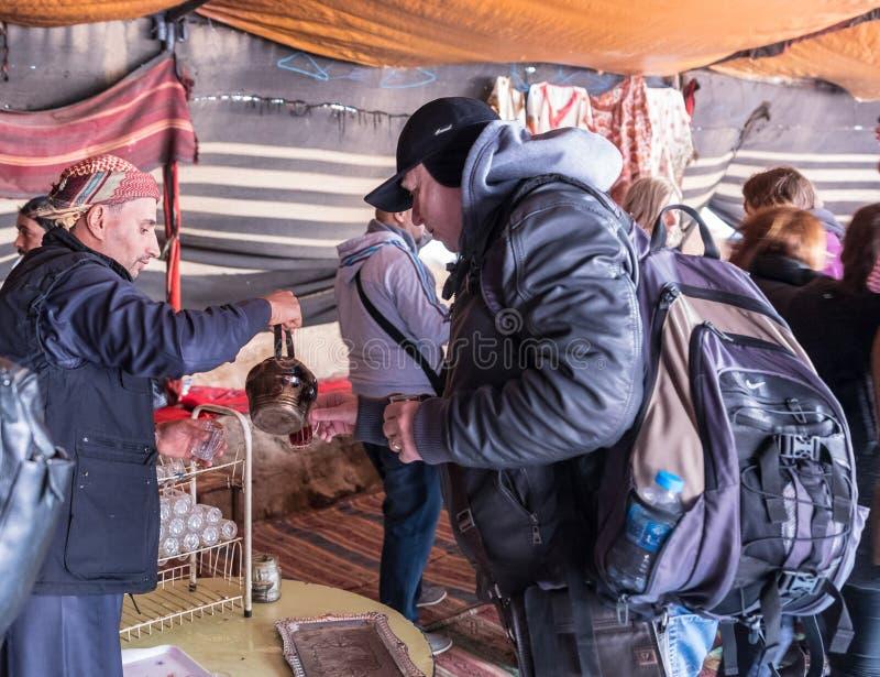 Beduine gießt Tee vom Kessel zum Touristen im Caravanserai in der Wadi Rum-Wüste nahe Aqaba-Stadt in Jordanien lizenzfreies stockbild