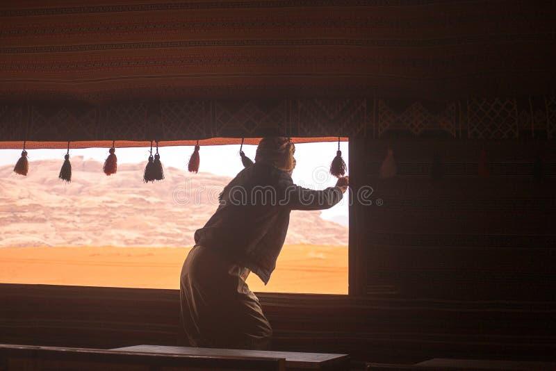 Beduinen öppnar fönstret av ett traditionellt tält arkivfoto
