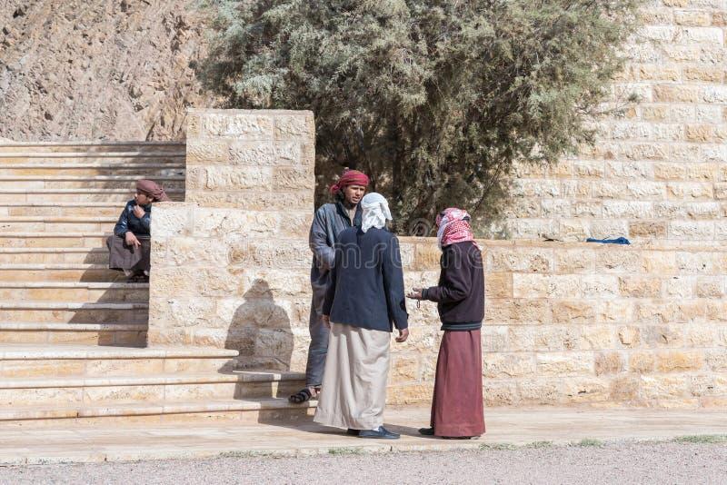 Beduiner - jeepchaufförer att stå och tala väntande på turister i Wadi Rum Visitor Center nära den Aqaba staden i Jordanien arkivfoton