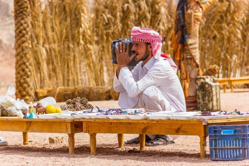 Beduino nel deserto e nel suo negozio di ricordo fotografia stock