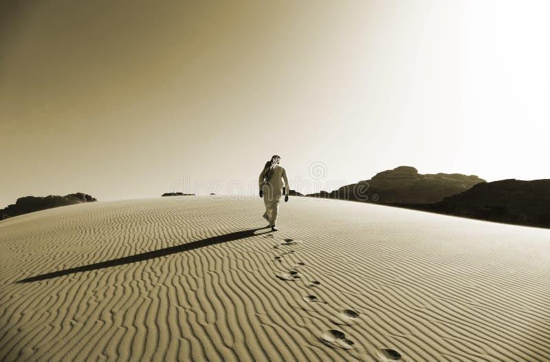 Beduino que camina en las dunas de arena en Wadi Rum Desert, Jordania en color de la sepia fotos de archivo libres de regalías