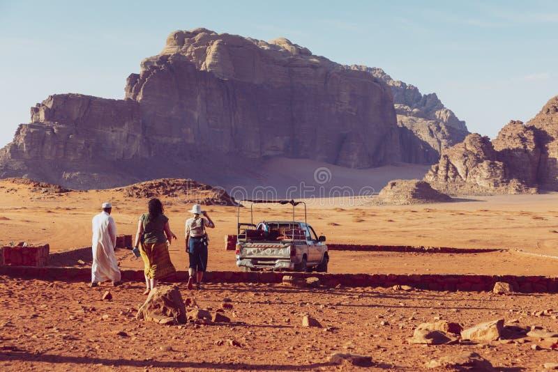Beduins biljeepar och turister, Wadi Rum ?ken i Jordanien, Mellan?sten royaltyfria foton