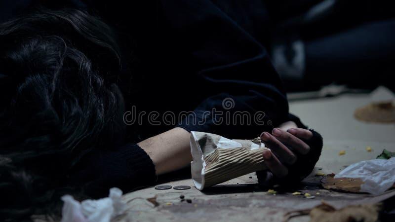 Bedwelmde dakloze het document van de vrouwenholding kop die op vloer in vuile schuilplaats ligt stock afbeelding