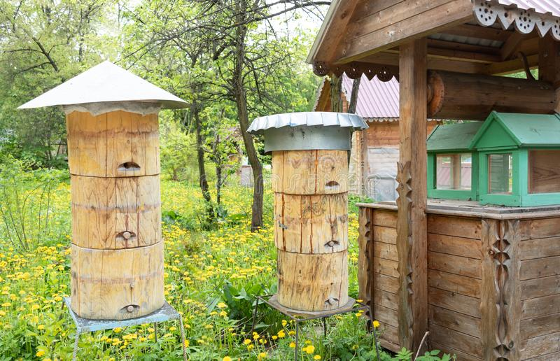 Bee hives with different types of metal roofs and wooden plugs. royalty free stock photography