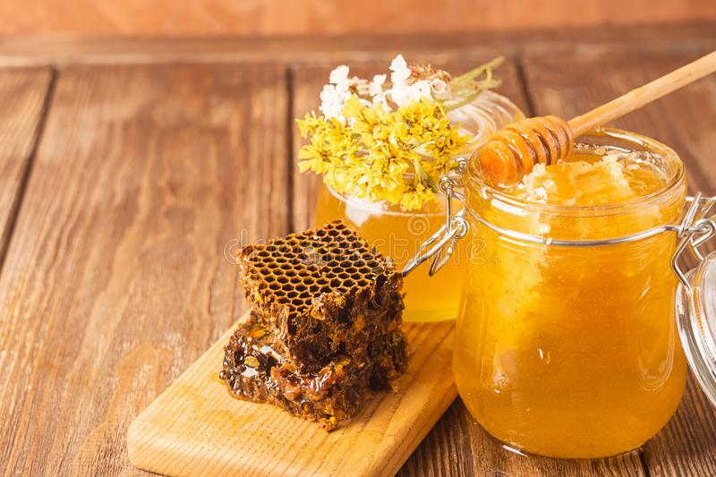 Bee honey in a glass jar and comb on a wooden background table. The concept of natural products. Horizontal frame. royalty free stock photo