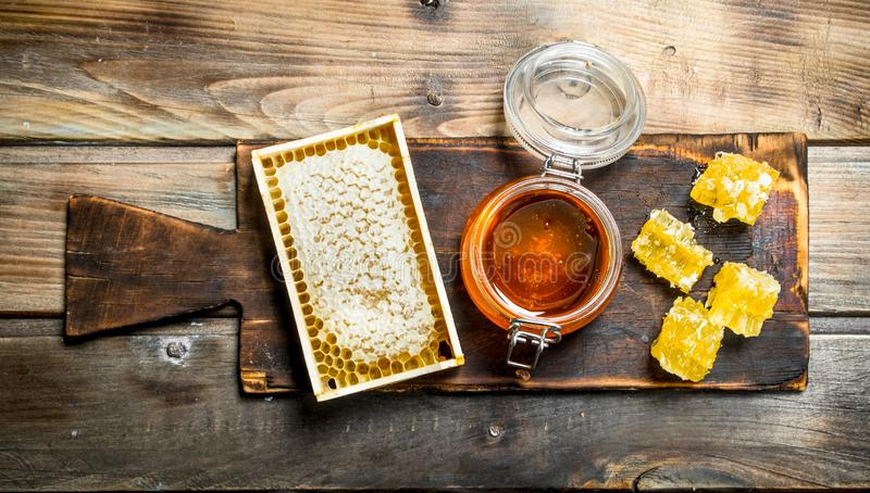 Bee honey on an old Board. On a wooden background stock photo