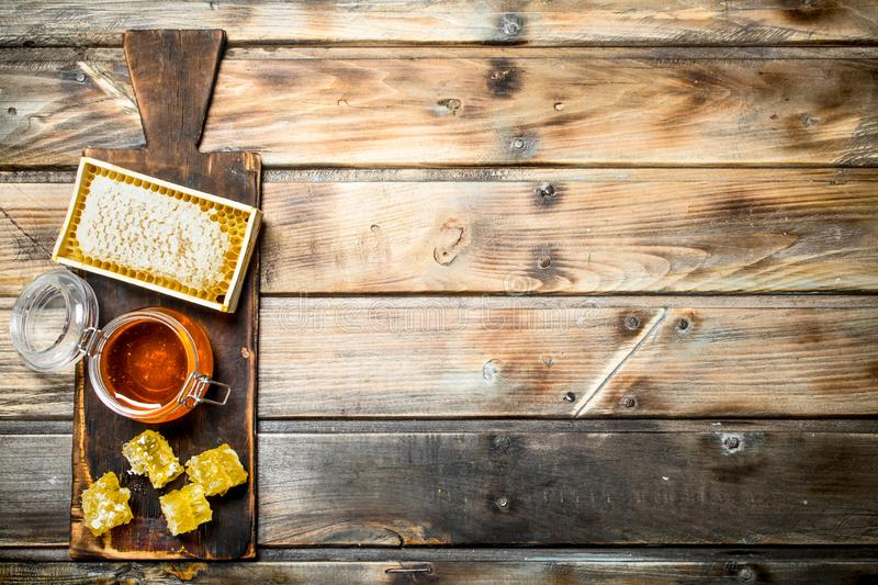 Bee honey on an old Board. On a wooden background royalty free stock photo