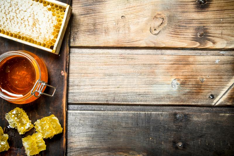 Bee honey on an old Board. On a wooden background royalty free stock photos