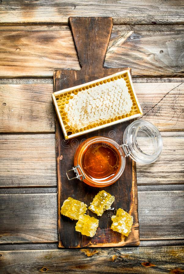 Bee honey on an old Board. On a wooden background stock photos