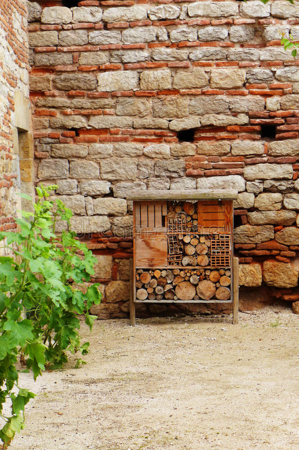 Bee hotel at medieval chateau. A medieval style bee hotel in the courtyard of an ancient French stone chateau house in Cahors, France. It is a beautiful rustic stock images