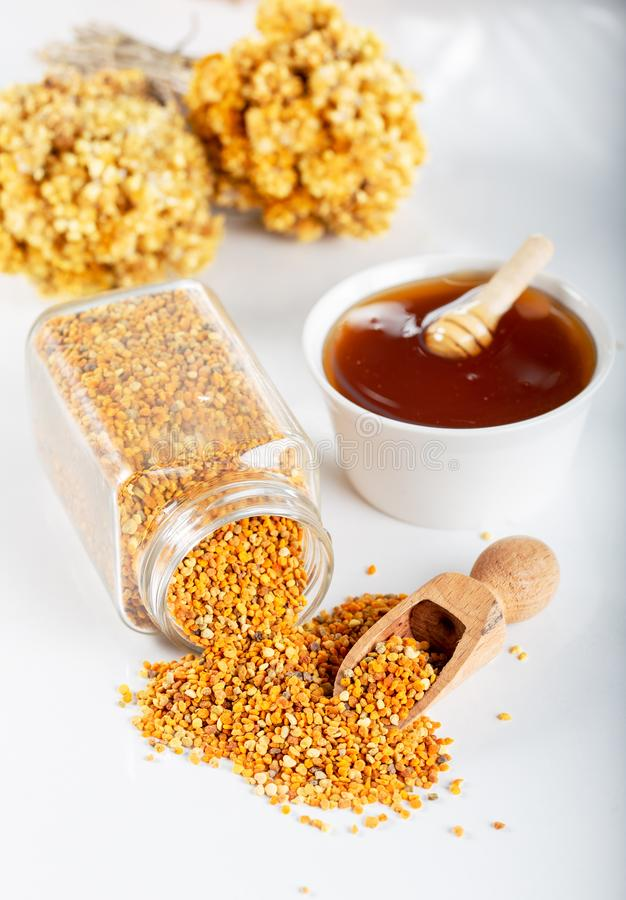 Bee pollen grains and honey in bowl. stock images