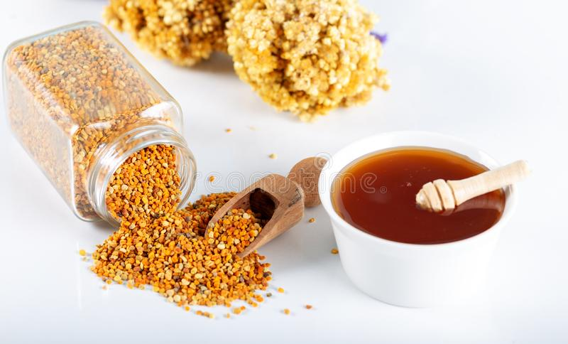 Bee pollen grains and honey in bowl. royalty free stock image