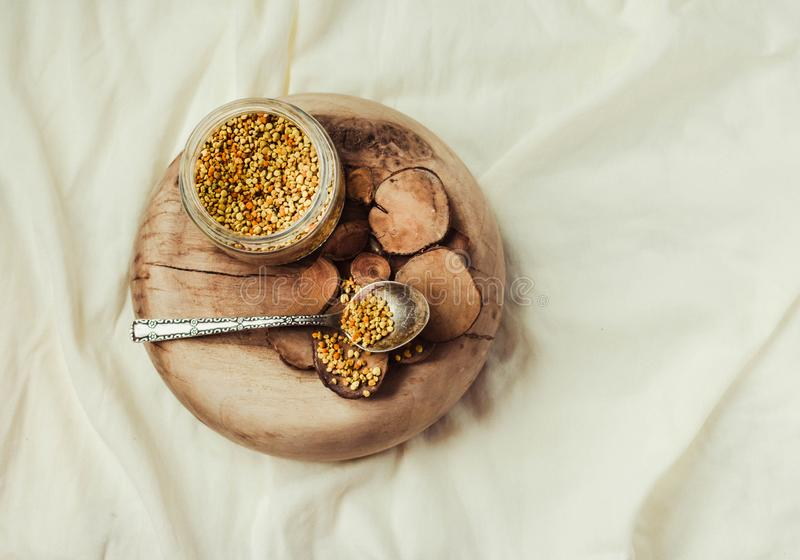 bee pollen in a jar on a wooden stand, white linen tablecloth.Copy space.Top view. stock photography