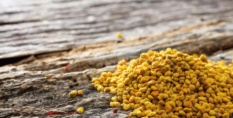 Bee pollen pile set on wooden surface.Closeup view. royalty free stock photos