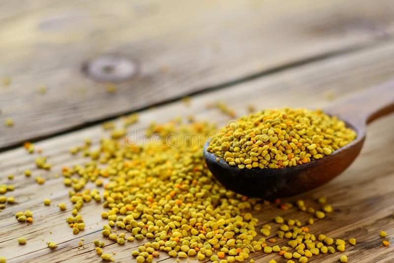 Bee pollen in spoon over wooden background. Healthy organic raw diet vegetarian food ingredient - bee pollen. Apitherapy. royalty free stock photography