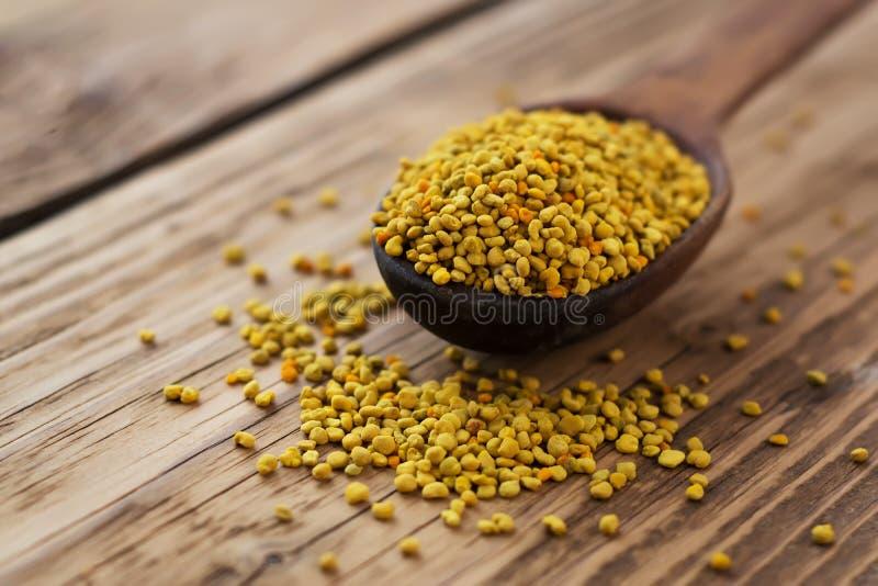 Bee pollen in spoon over wooden background. Healthy organic raw diet vegetarian food ingredient - bee pollen. Beekeeping products. stock photography