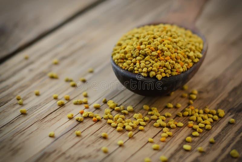 Bee pollen in spoon over wooden background. Healthy organic raw diet vegetarian food ingredient - bee pollen. Beekeeping products. stock image