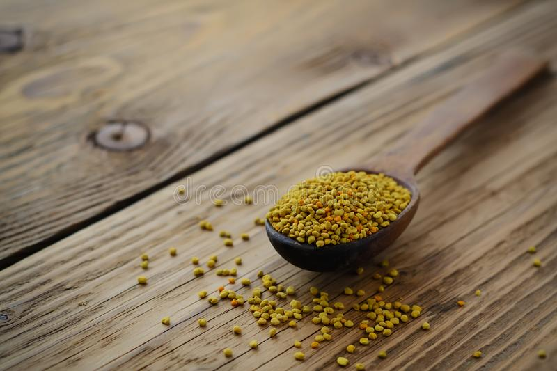 Bee pollen in spoon over wooden background. Healthy organic raw diet vegetarian food ingredient - bee pollen. Beekeeping products. royalty free stock photography