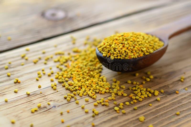 Bee pollen in spoon over wooden background. Healthy organic raw diet vegetarian food ingredient - bee pollen. Apitherapy. stock images