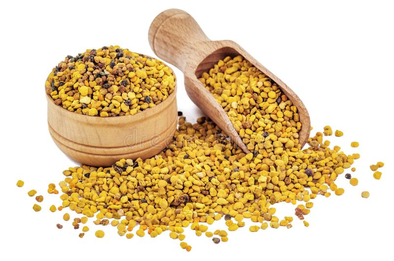 Bee pollen and wooden scoop on white royalty free stock photos