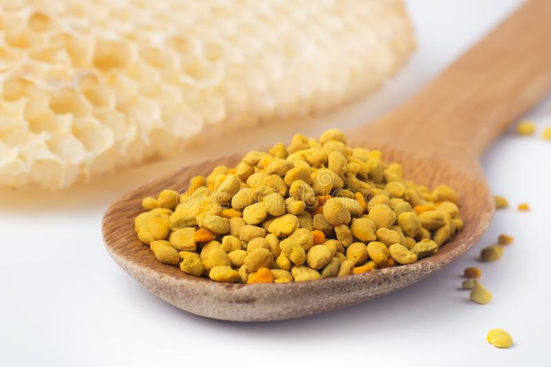 Bee pollen in a wooden spoon and a honeycomb. Beekeeping products. Apitherapy. royalty free stock photography