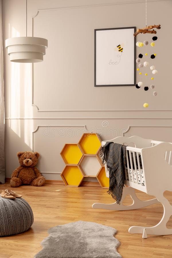 Bee poster, honeycombs, teddy bear on the floor and crib in a toddler room interior. Real photo royalty free stock images