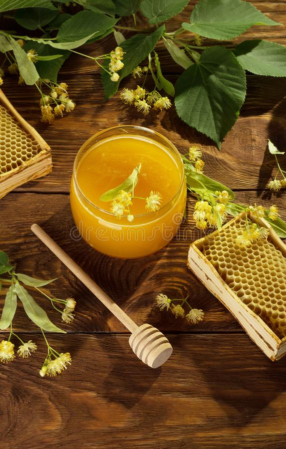 Bee products and wooden honey agitator, on brown surface stock photography