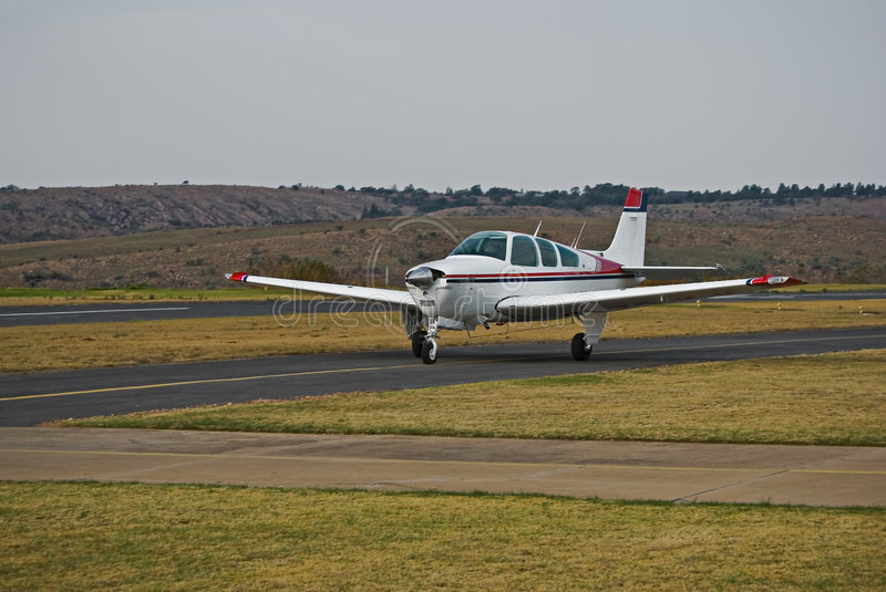 Beechcraft Bonanza - Wider Angle. Ready, Steady, Fly … This light aircraft [Beechcraft Bonanza] is taxiing down the runway to get airborne stock image