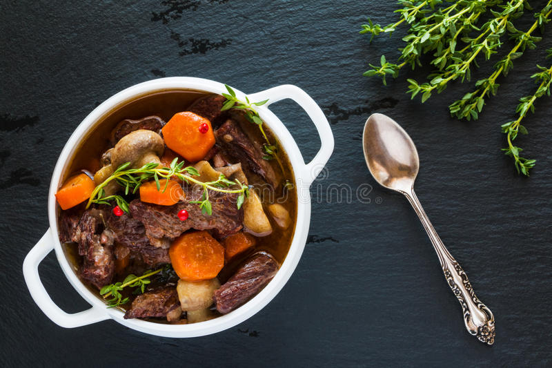 Beef Bourguignon in a white soup bowl on black stone background, top view. Stew with carrots, onions, mushrooms, bacon. Garlic and bouquet garni. The dish is royalty free stock photography