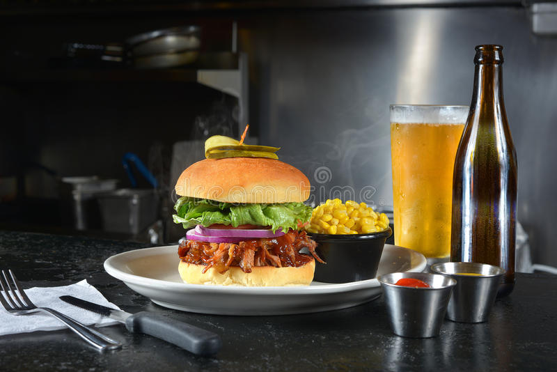 Beef brisket burger and beer. A juicy beef brisket burger with corn, ketchup, and mustard with an ice cold glass of beer stock photos