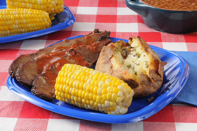 Beef brisket with corn on the cob. A plate of beef brisket with barbecue sauce, corn on the cob and a baked potato stock image