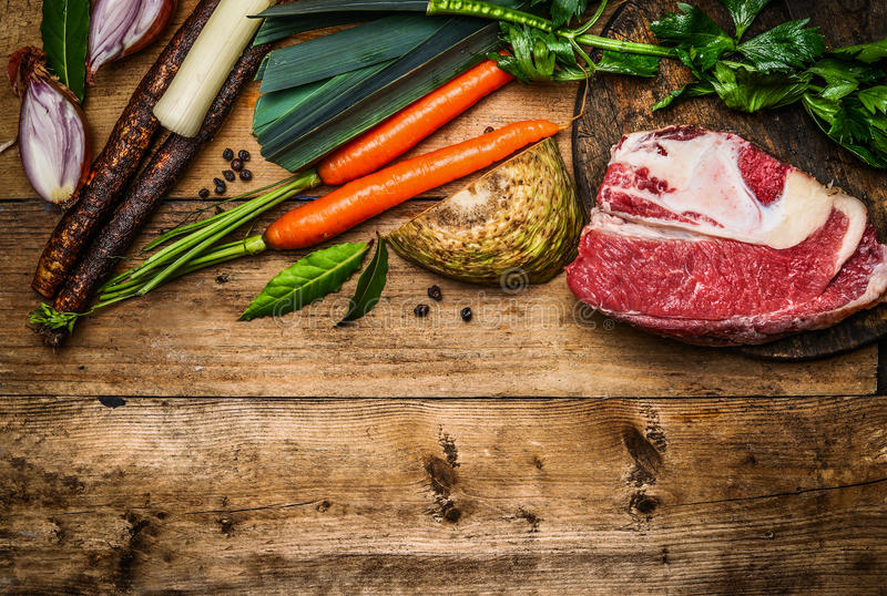 Beef brisket with vegetables ingredients for soup or broth cooking on rustic wooden background, top view. Border royalty free stock images