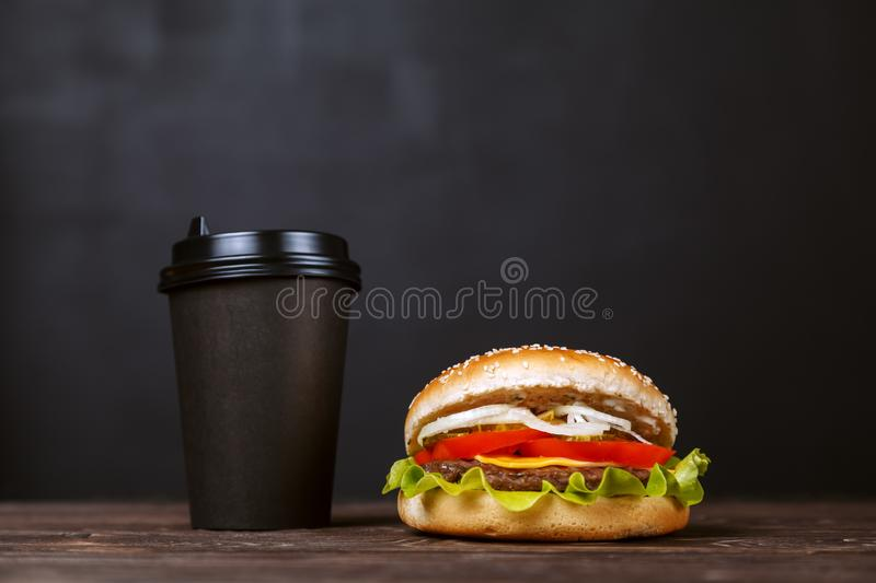Beef Burger with bacon and coffee in a black paper Cup on a wooden table on a dark background. Cafe menu design concept royalty free stock images
