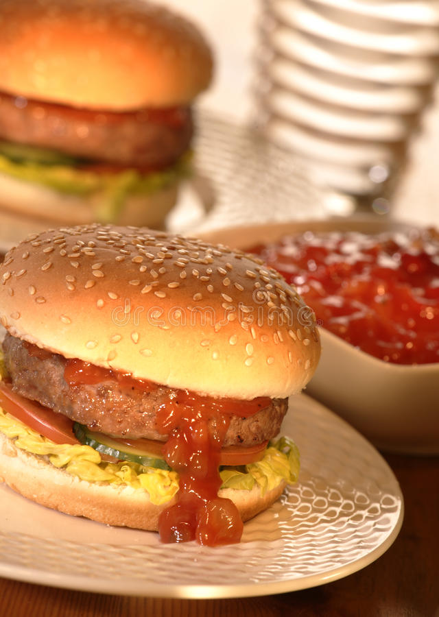 BEEF BURGER IN BUN WITH SALAD AND RELISH. WITH ANOTHER BURGER IN BACKGROUND stock photos
