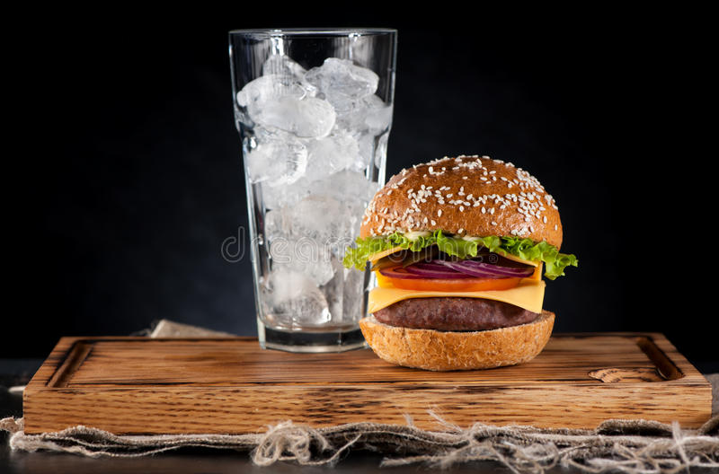 Beef burger. Homemade beef burger and a glass with ice stock photos
