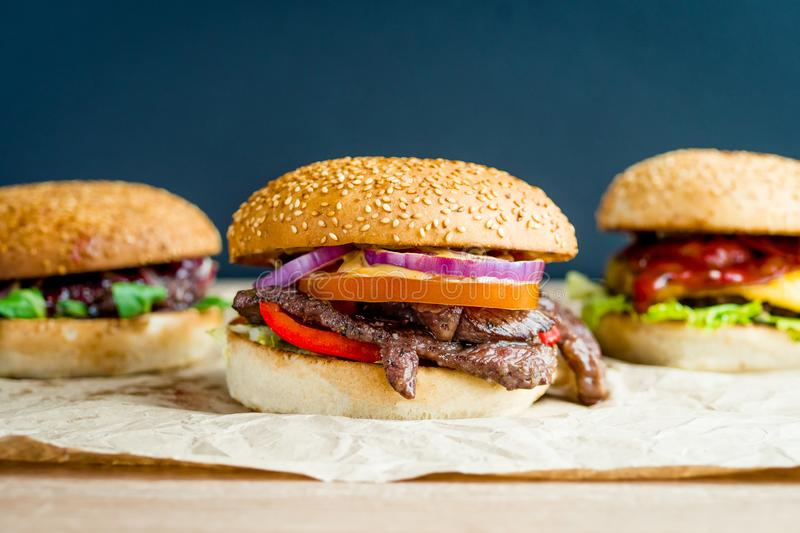 Beef burger with tomato, salad, onion, pepers and cheese royalty free stock images