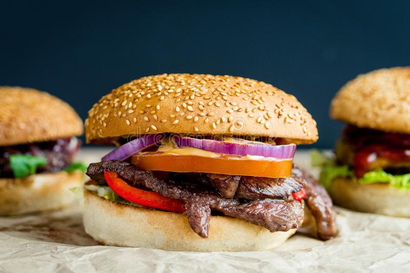 Beef burger with tomato, salad, onion, pepers and cheese royalty free stock photography