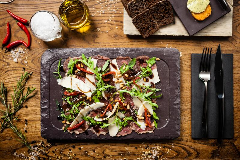 Beef carpaccio served on a board in restaurant royalty free stock photo