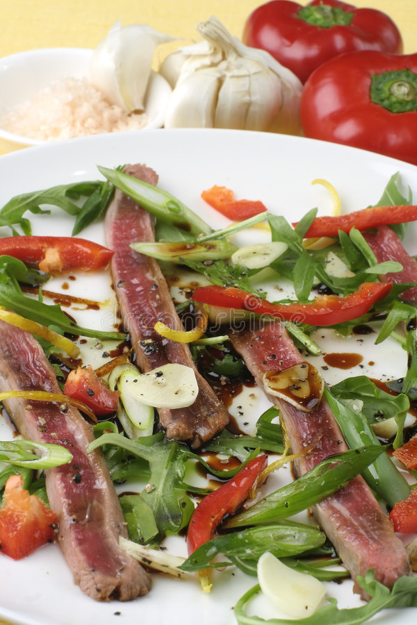 Beef carpaccio; salad and ingredients. Finely sliced raw bleu beef with rocket and baby capsicum. Sharp view of salad with ingredients in background against royalty free stock photography