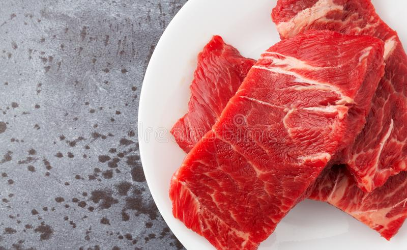 Beef chuck boneless short rib steaks on a white plate on a gray counter top close view. Top close view of several pieces of beef chuck boneless short rib royalty free stock photography