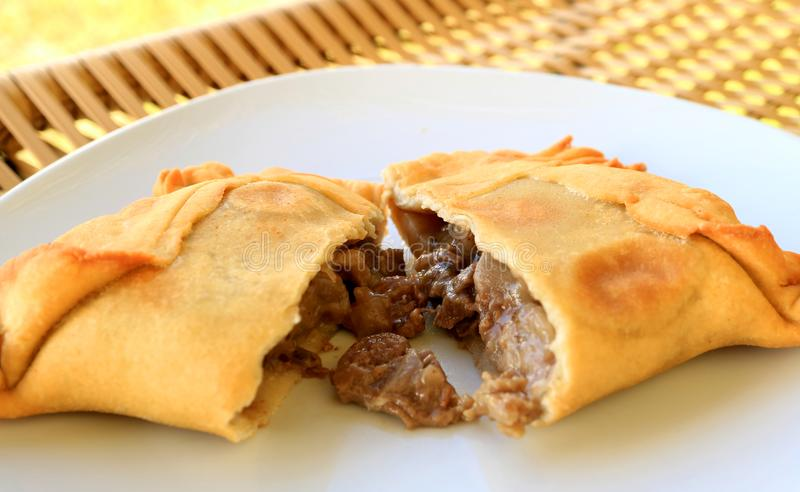Beef filled Empanada or Empanada de Pino, delicious Chilean baked pasty served on white plate. Traditional food stock photo