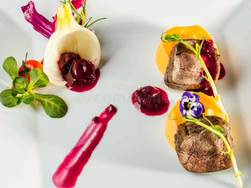 Beef fillet mignon. Grilled and garnished meat with colorful vegetables red berry sauce decorated with flower on white background royalty free stock images