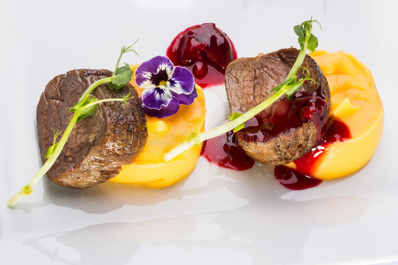 Beef fillet mignon. Grilled and garnished meat with colorful vegetables red berry sauce decorated with flower on white background stock images