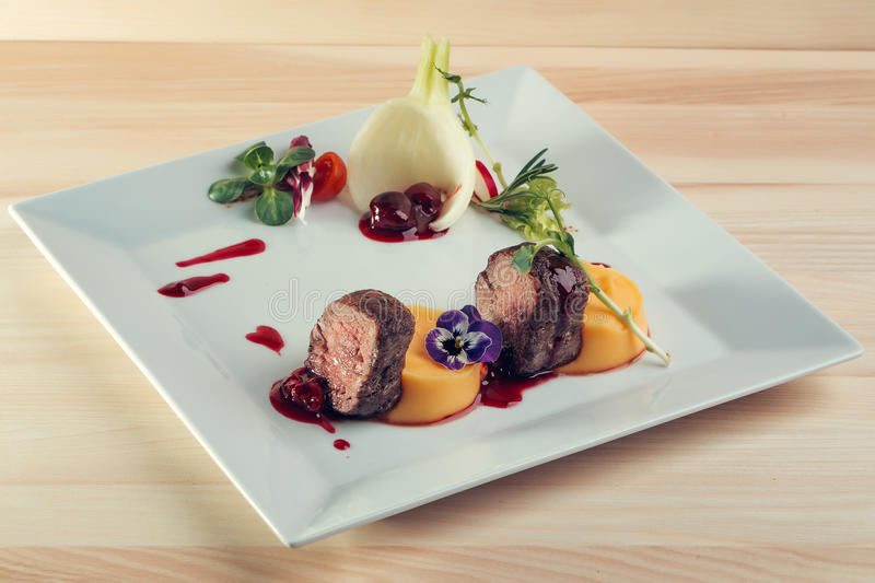 Beef fillet mignon. Grilled and garnished meat with colorful vegetables red berry sauce decorated with flower on wooden background royalty free stock photo