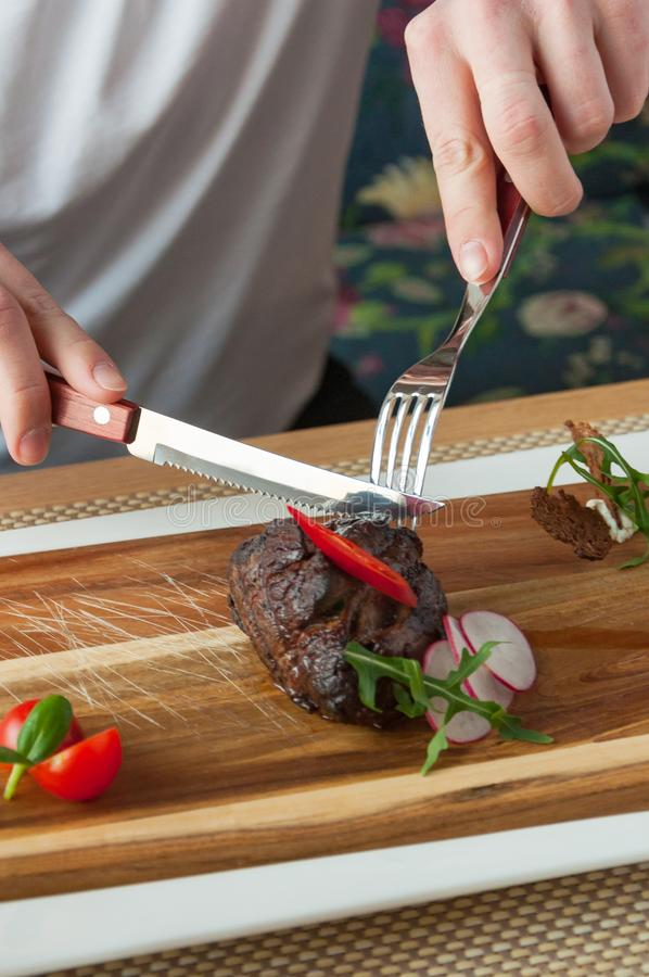 Beef fillet Mignon medium roasting on a wooden Board. Juicy beef fillet Mignon medium roasting on a wooden Board royalty free stock image