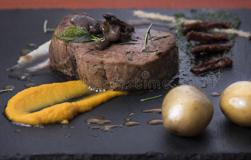 Beef fillet with mushrooms,sundried tomatoes and vegetable puree on a slate plate 7 stock photography